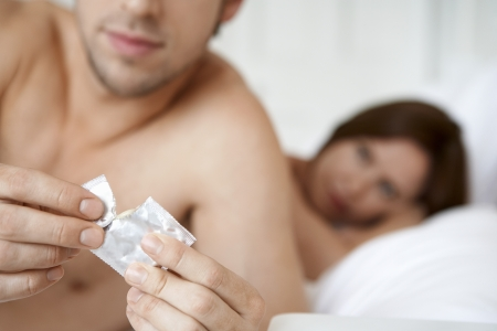 safe sex: Couple in bed man opening condom close up of condom