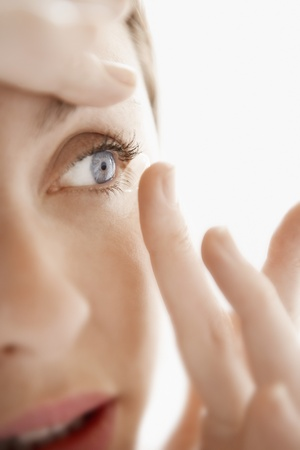 contact lens: Woman Inserting Contact Lens close up of face LANG_EVOIMAGES