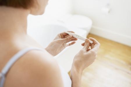 prueba de embarazo: Mujer que controla Pregnancy Test Kit secci�n media foco en las manos
