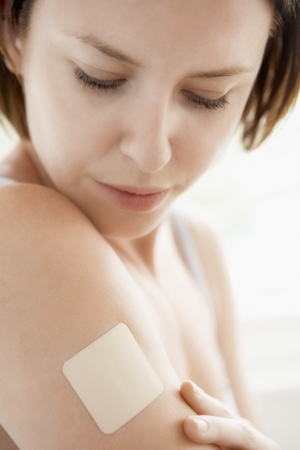 nicotine patch: Woman looking at nicotine patch on arm close up
