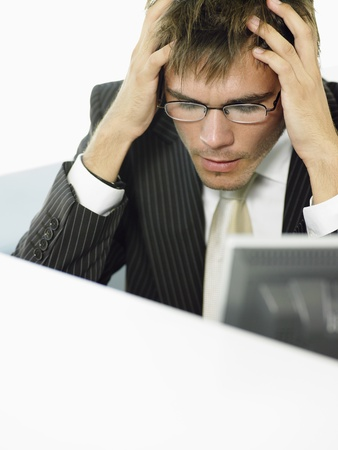 anguished: Stressed Businessman sitting at desk by computer