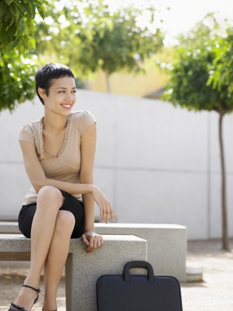 Smiling Businesswoman sitting on bench in plaza Stock Photo