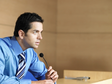 Businessman in conference room talking into microphone