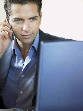 Businessman Using Cell Phone and Laptop Indoors Stock Photo - 19213656