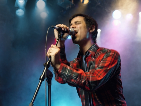 anguished: Young Man Singing into microphone on stage at Concert low angle view