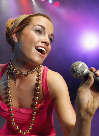 Young Woman Singing on stage in Concert close up low angle view Stock Photo - 19327148