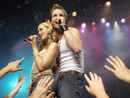 Young man and woman singing on stage in concert in front of adoring fans low angle view Stock Photo
