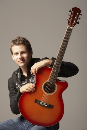 half length posed: Young Man sitting with Acoustic Guitar smiling portrait LANG_EVOIMAGES