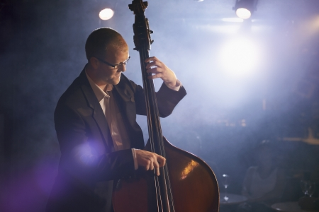 late thirties: Man Playing Double Bass in Jazz Club