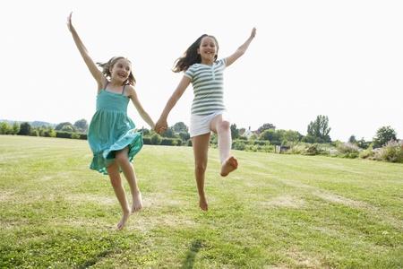 Girls Running and jumping Hand in Hand through field Standard-Bild