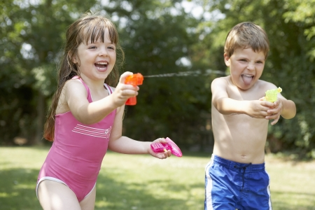 two piece swimsuits: Girl and boy in backyard shooting water pistols LANG_EVOIMAGES