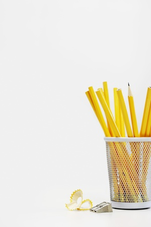 pencil sharpener: Group of yellow pencils in holder by sharpener