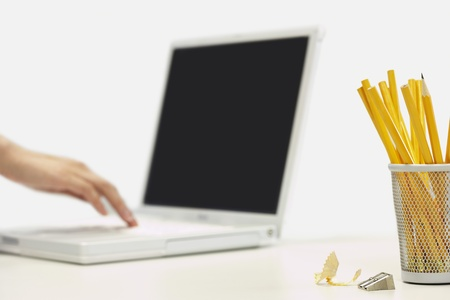 Pencils and sharpener by person using laptop focus on foreground Stock Photo - 19075906