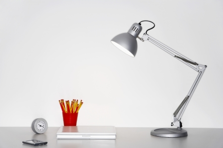 Angle poise lamp laptop clock pencils and PDA on desk Stock Photo - 19075917
