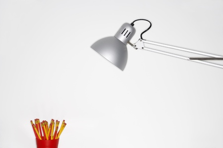 Angle poise lamp shining on cup of pencils Stock Photo - 19075918