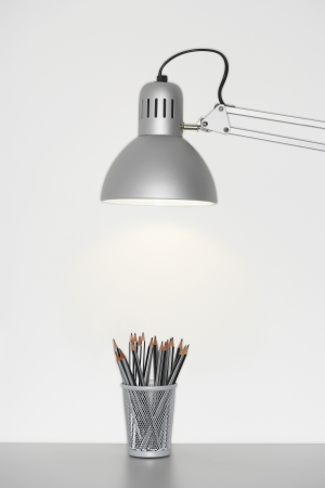 Angle poise lamp shining on cup of pencils Stock Photo - 19075920