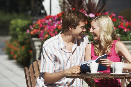 guidebook: Young couple sitting at outdoor cafe laughing and holding guidebook
