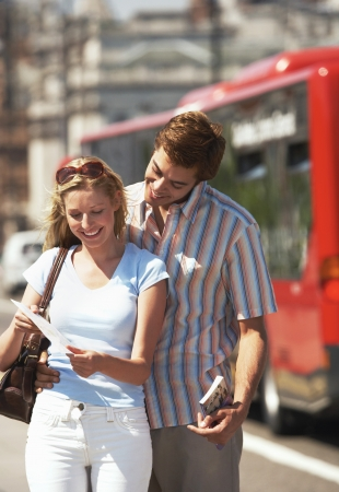 vacationing: Young vacationing couple on London street reading map
