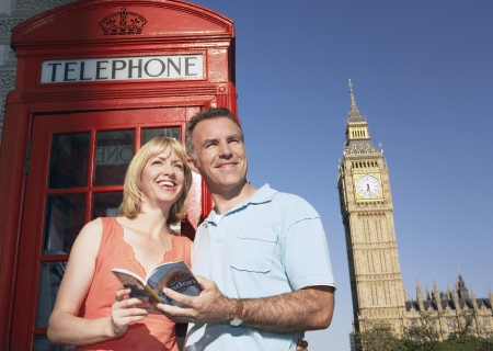 guidebook: Couple with guidebook standing by London phone booth