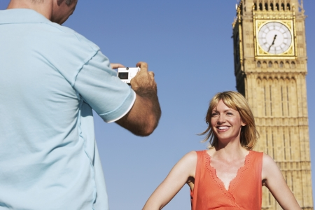 taking a wife: Husband taking photo of wife by Big Ben Tower London England