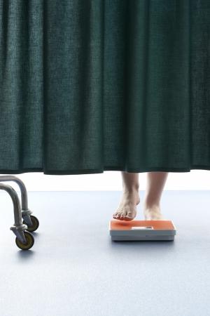 weighing scales: Persona salire su bilance, dietro la tenda in ospedale, basso sezione