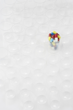Plastic cup containing pills, surrounded by empty glasses Stock Photo - 18884795