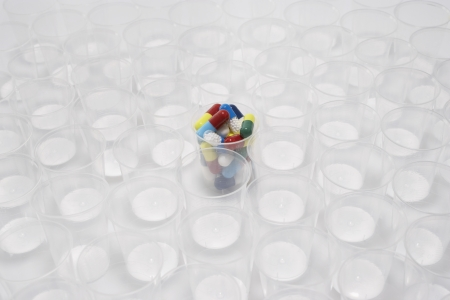 Plastic cup containing pills, surrounded by empty glasses Stock Photo - 18884842