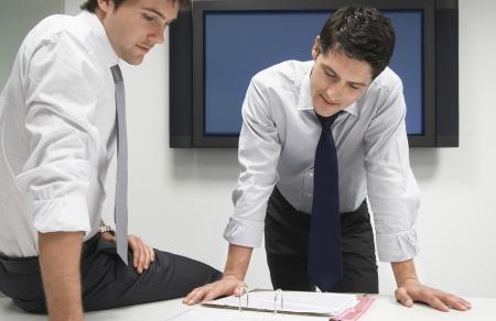 toma de decision: Dos hombres de negocios buscan en la carpeta de archivos