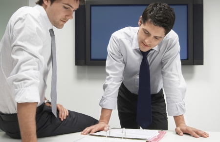 discussed: Two Businessmen Looking in File Folder LANG_EVOIMAGES