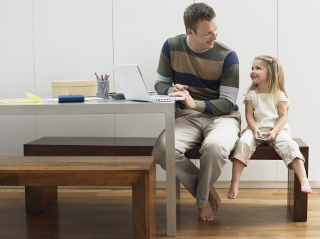 wood panelled: Father and daughter using laptop and cell phone LANG_EVOIMAGES