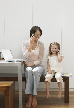 wood panelled: Mother and daughter using cell phones LANG_EVOIMAGES