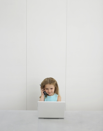 Small girl by desk using cell phone and laptop Stock Photo - 19075936