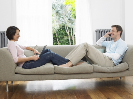 Couple reclining on couch using laptop and cell phone Stock Photo - 19327168
