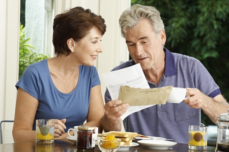 couple talking: Middle-aged couple looking at bill over breakfast