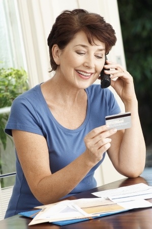 paying with credit card: Woman paying credit card using cell phone LANG_EVOIMAGES