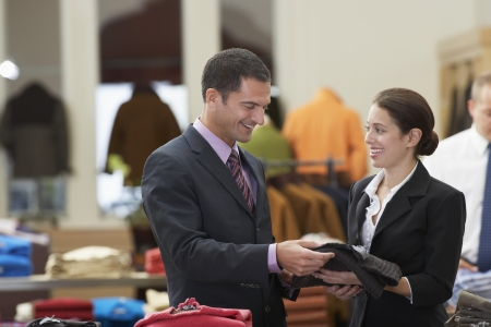 two people with others: Man in Clothing Store