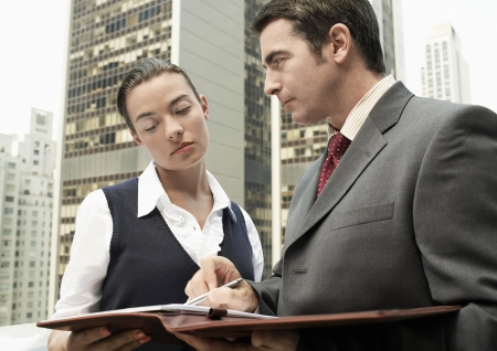 half  length: Business man showing paperwork to business woman outdoors in city half length LANG_EVOIMAGES