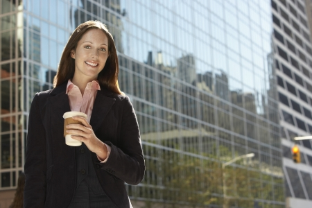 low blouse: Office worker with drink outside office building portrait