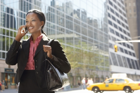 Businesswoman using mobile phone in street Stock Photo