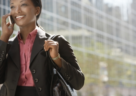 business woman standing: Businesswoman using mobile phone outdoors