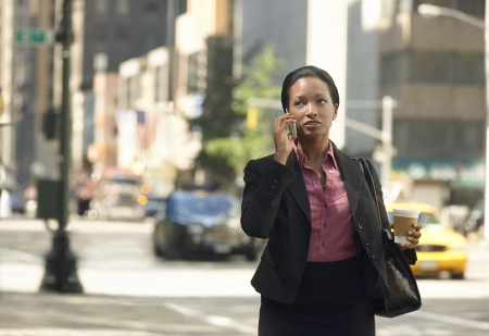 Businesswoman using mobile phone in street Stock Photo - 19075956