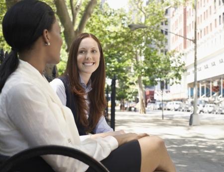 sidewalk talk: Two female colleagues talking in street