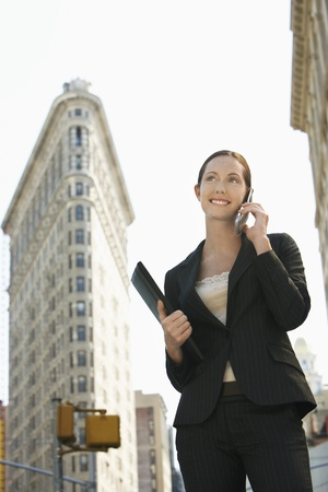Businesswoman using mobile phone in street Stock Photo - 19075959