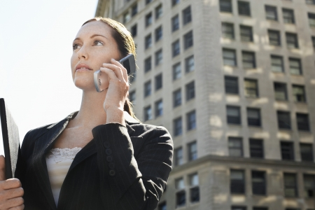 Businesswoman using mobile phone in street Stock Photo - 19184584