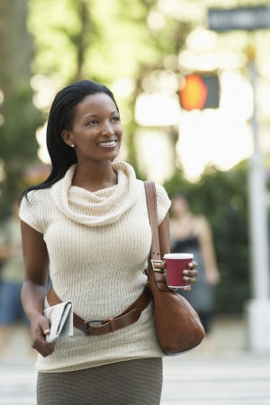 Woman with newspaper and coffee cup walking in street Stock Photo - 19213718
