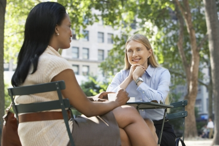 Female colleagues sitting at street cafe Stock Photo - 19213503