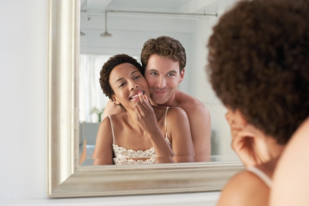 late 20s: Man Hugging Woman as She Applies Lipstick