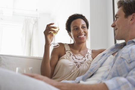 racially diverse: Couple Drinking Wine on Sofa