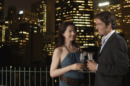nighttimes: Elegant Couple on a Date against nighttimes cityscape