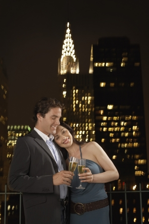 couple lit: Couple Toasting with Champagne against New York Night Skyline